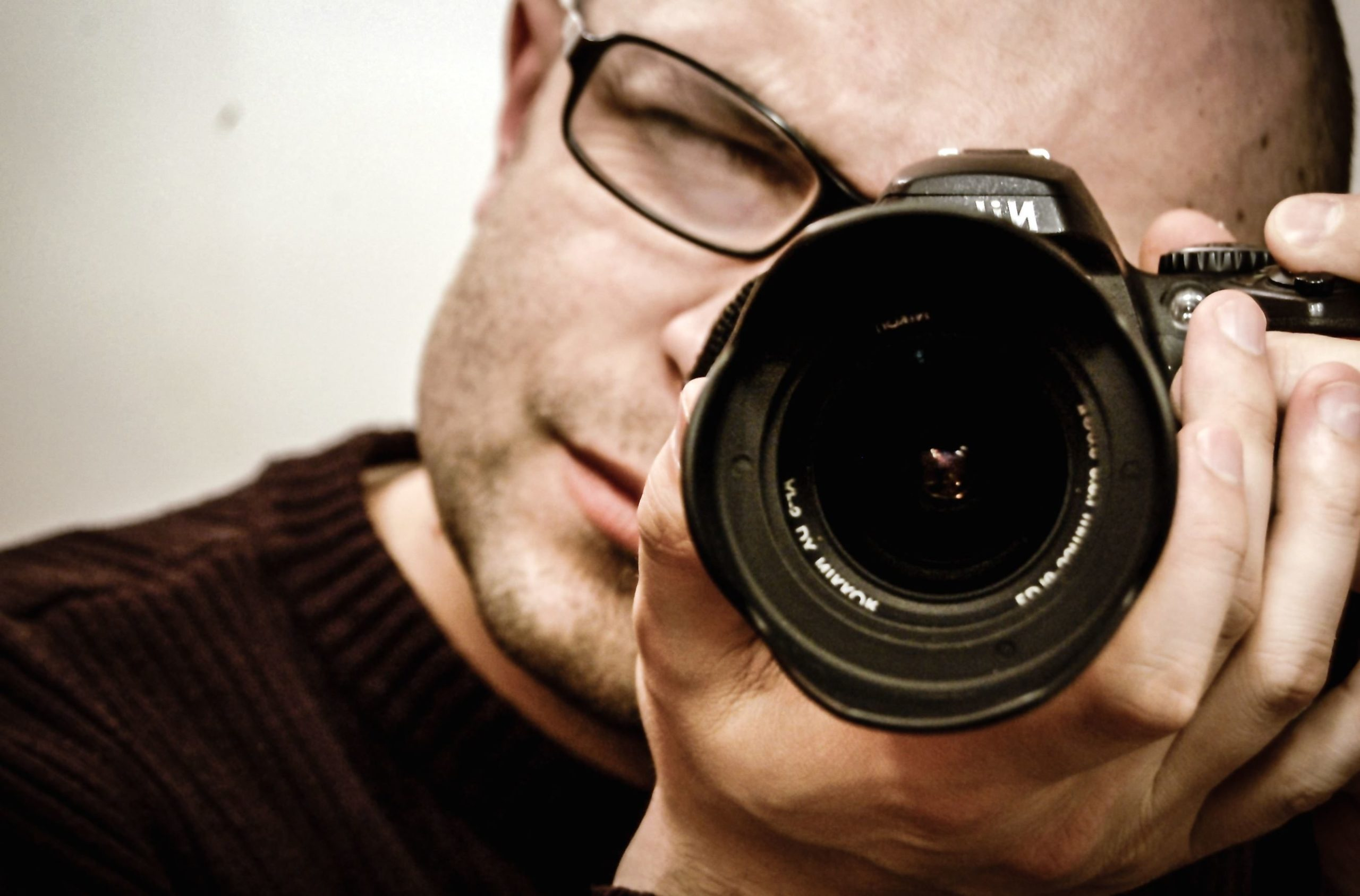 Primo piano di un fotografo nell'atto di scattare una fotografia